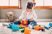 Sweet child playing with plastic blocks