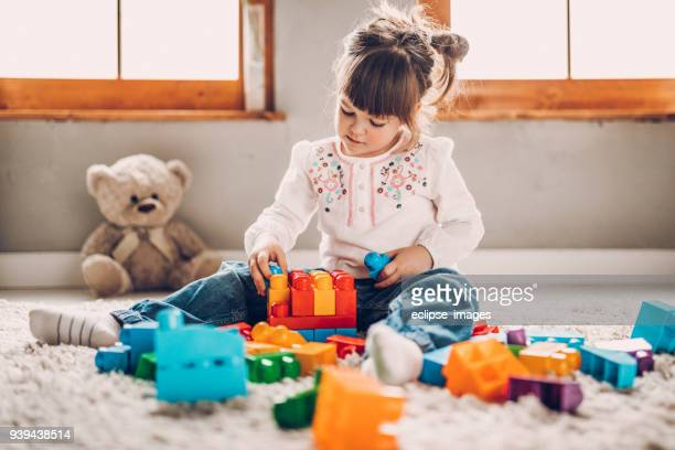 sweet child playing with plastic blocks - giochi per bambini foto e immagini stock