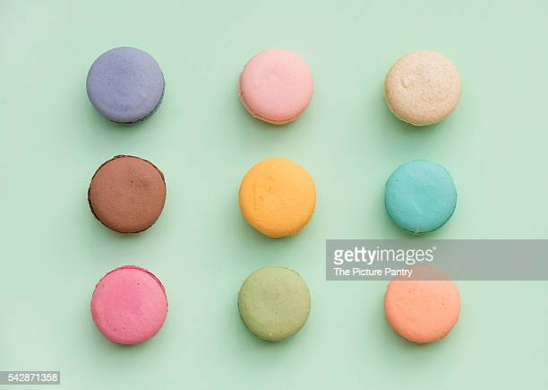 Sweet colorful French macaroon biscuits on pastel mint background