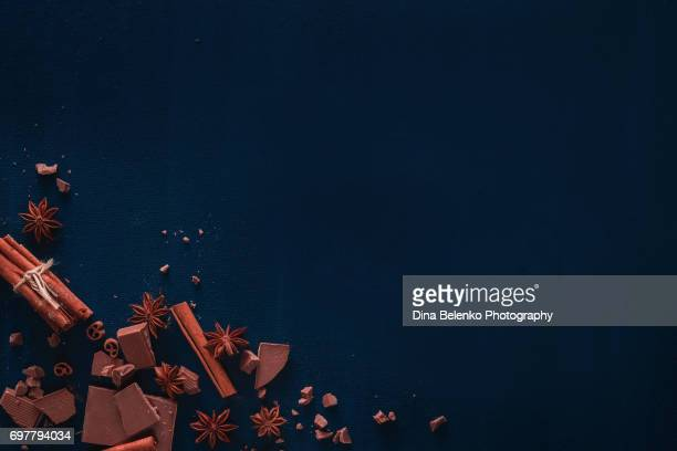 Sweet copy space frame with cocoa powder, chocolate and cinnamon on a black background