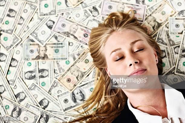 Sweet dreams as beautiful blonde sleeps on pile of dollars