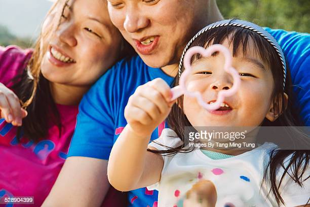 Sweet family playing bubbles in park joyfully