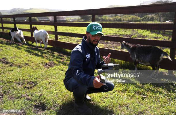 """Sweet Farm co-founder Nate Salpeter uses his iPhone to speak to a group during a """"Goat 2 Meeting"""" Zoom meeting on May 01, 2020 in Half Moon Bay,..."""