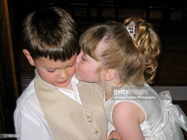 Sweet flower girl kissing ring bearer