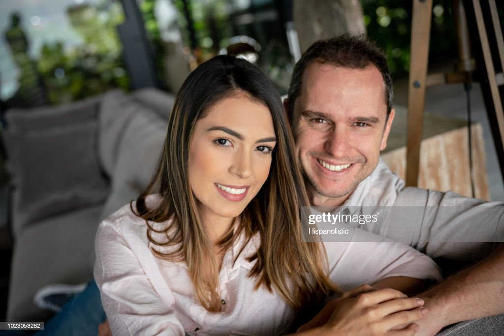 Sweet latin american couple at home looking at camera smiling while sitting on couch : Stock Photo