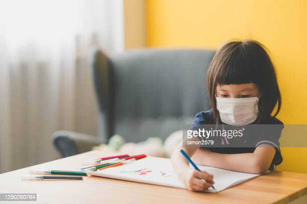 sweet little asian girl wear protective face mask sitting at desk and drawing with a color pen at living room - mask cartoon characters stock pictures, royalty-free photos & images
