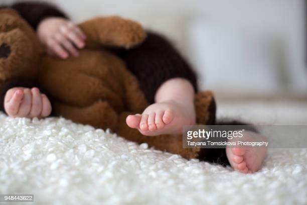 sweet little baby boy, dressed in handmade knitted brown soft teddy bear overall, sleeping cozy at home in sunny bedroom with lots of teddy bears around him - soft toy stock pictures, royalty-free photos & images