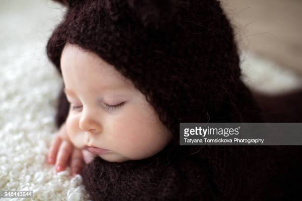 Sweet little baby boy, dressed in handmade knitted brown soft teddy bear overall, sleeping cozy at home in sunny bedroom with lots of teddy bears around him