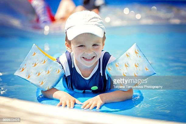 Sweet little boy, swimming in big swimming pool