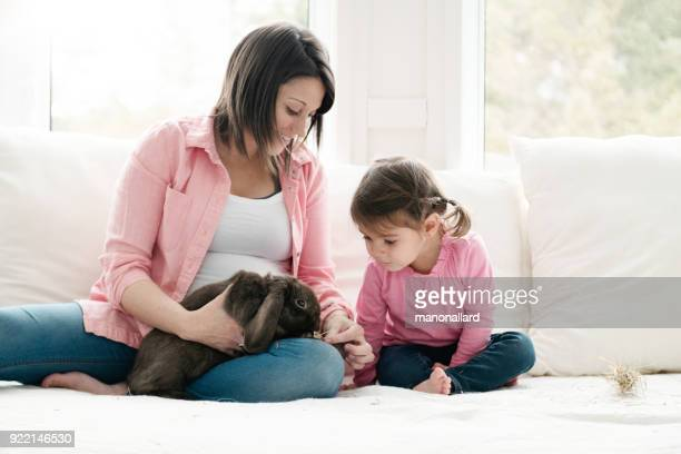 Sweet little girl and her mom sit on bed with a cute rabbit ram during easter holidays