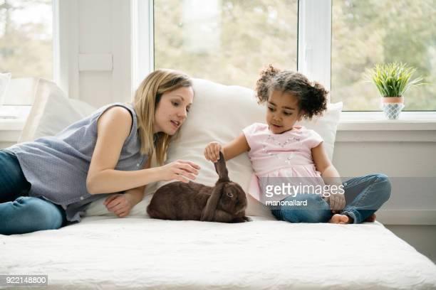 Douce petite fille et sa maman s'asseoir sur le lit avec un bélier lapin mignon pendant les vacances de Pâques