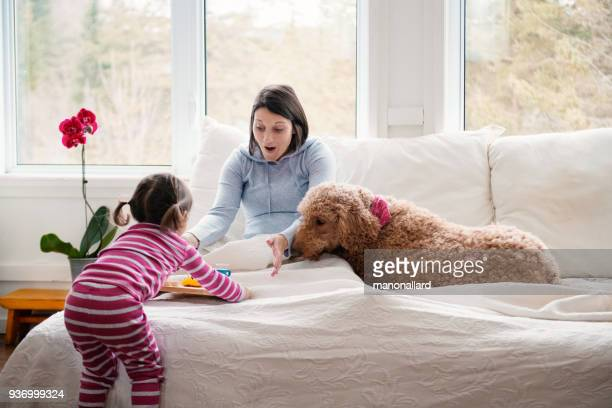 sweet little girl brings breakfast at bed during mother's day - festa della mamma foto e immagini stock
