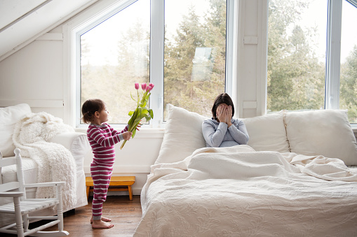 Sweet little girl brings tulips flowers at bed during Mother's day 937002126