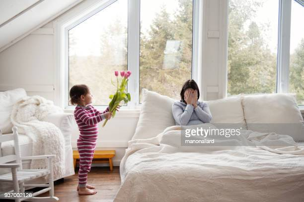 sweet little girl brings tulips flowers at bed during mother's day - festa della mamma foto e immagini stock