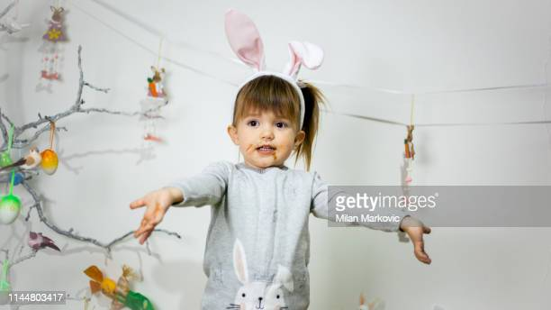 sweet little girl dirty with chocolate wearing bunny ears and eating chocolate on easter - dirty easter stock pictures, royalty-free photos & images