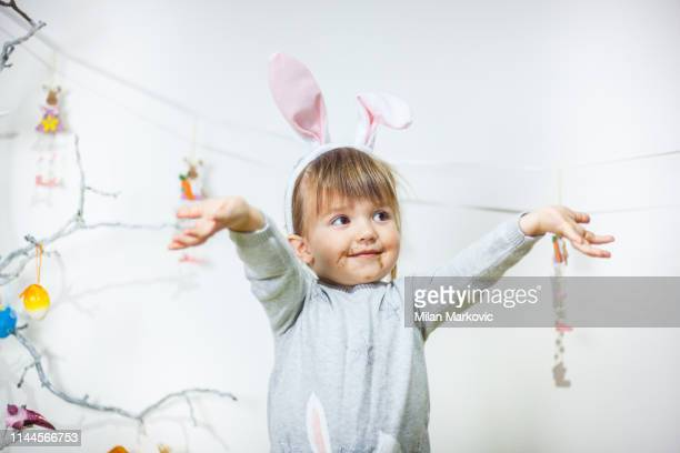 sweet little girl dirty with chocolate wearing bunny ears and playing egg hunt on easter - dirty easter stock pictures, royalty-free photos & images