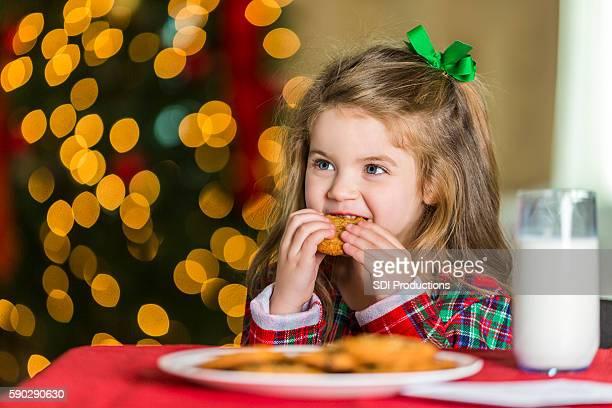 Sweet little girl eating Christmas cookies