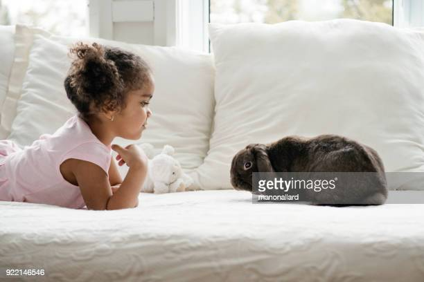 Sweet little girl lying on bed with a cute rabbit ram during easter holidays