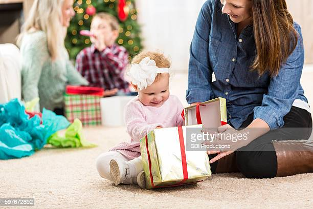 Sweet little girl opens a Christmas present with her mother