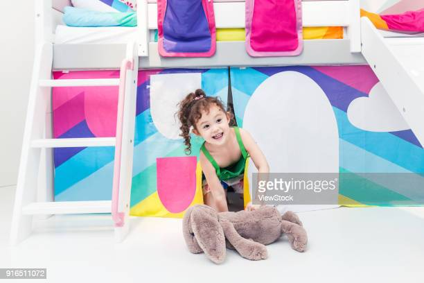 Sweet little girl playing in the bedroom