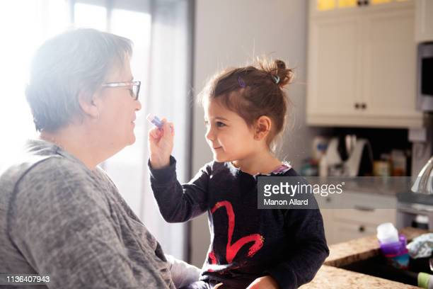 sweet little girl put lipstick to her grandmother - chubby granny fotografías e imágenes de stock