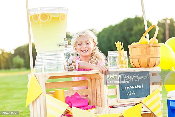 Sweet little girl sitting behind her lemonade stand