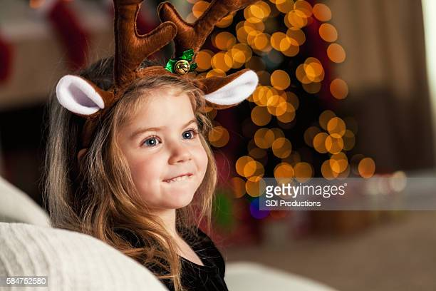 Sweet little girl wears reindeer ears and antlers
