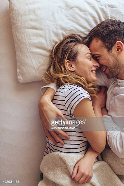 sweet mornings - romantic young couple sleeping in bed stock photos and pictures