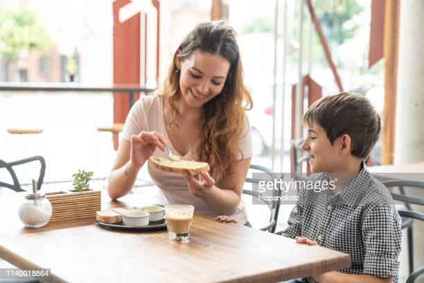 sweet mother and son enjoying a breakfast, mother spreading butter on toast while both talking very cheerfully - hispanolistic stock photos and pictures