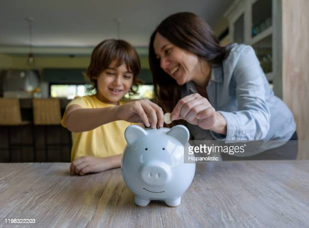 sweet mother and son inserting coins into a piggy bank at home - family with one child stock pictures, royalty-free photos & images