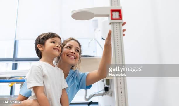 enfermeira e menino doces que olham quanto é crescido ambos muito felizes - pediatra - fotografias e filmes do acervo