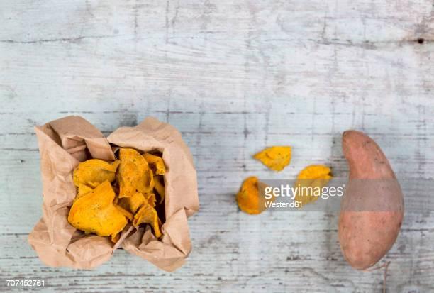 Sweet potato chips and fresh sweet potato on wood
