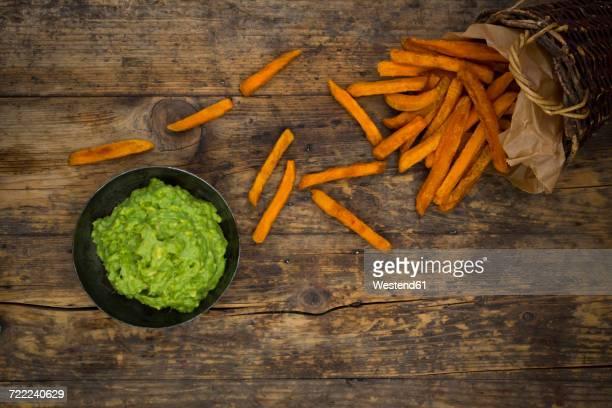 Sweet potato fries and avocado dip on wood