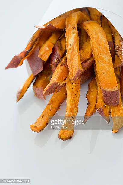 Sweet Potato fries in paper bag, close up, studio shot