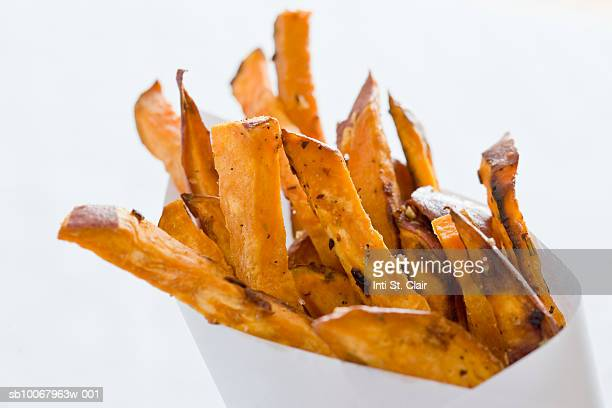 Sweet Potato fries in paper bag, close up, studio shot