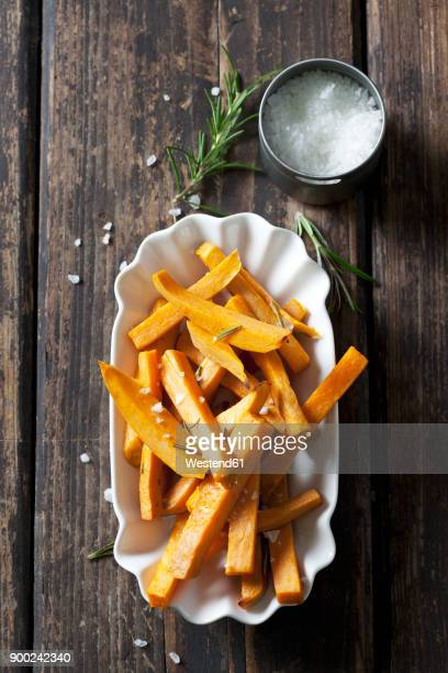 Sweet potato fries with rosmary and salt in porcelain bowl