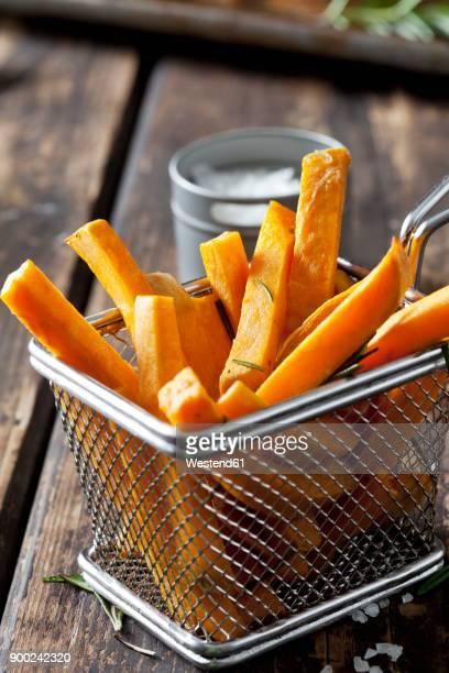 sweet potato fries with rosmary in chip basket - fries stock-fotos und bilder