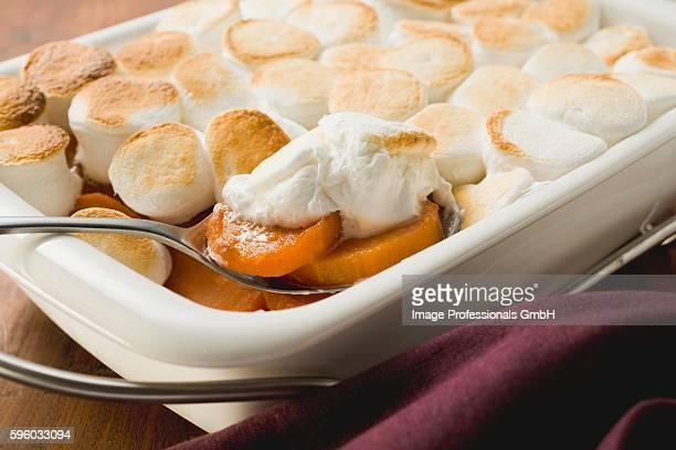 Sweet potato & marshmallow gratin in baking dish with spoon
