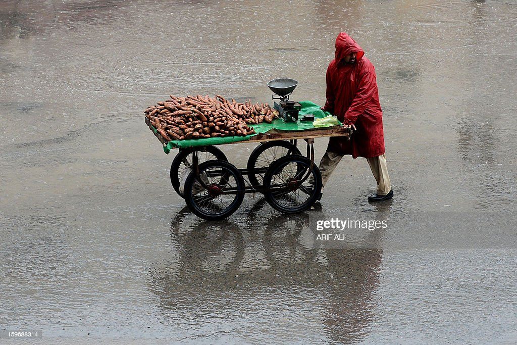 A sweet potato vendor pushes his cart in the rain in Lahore on January 18, 2013. The Pakistan Meteorological Department (PMD) on Thursday forecast rain with snowfall over the hills at scattered places of province Punjab including Islamabad. AFP PHOTO/Arif ALI