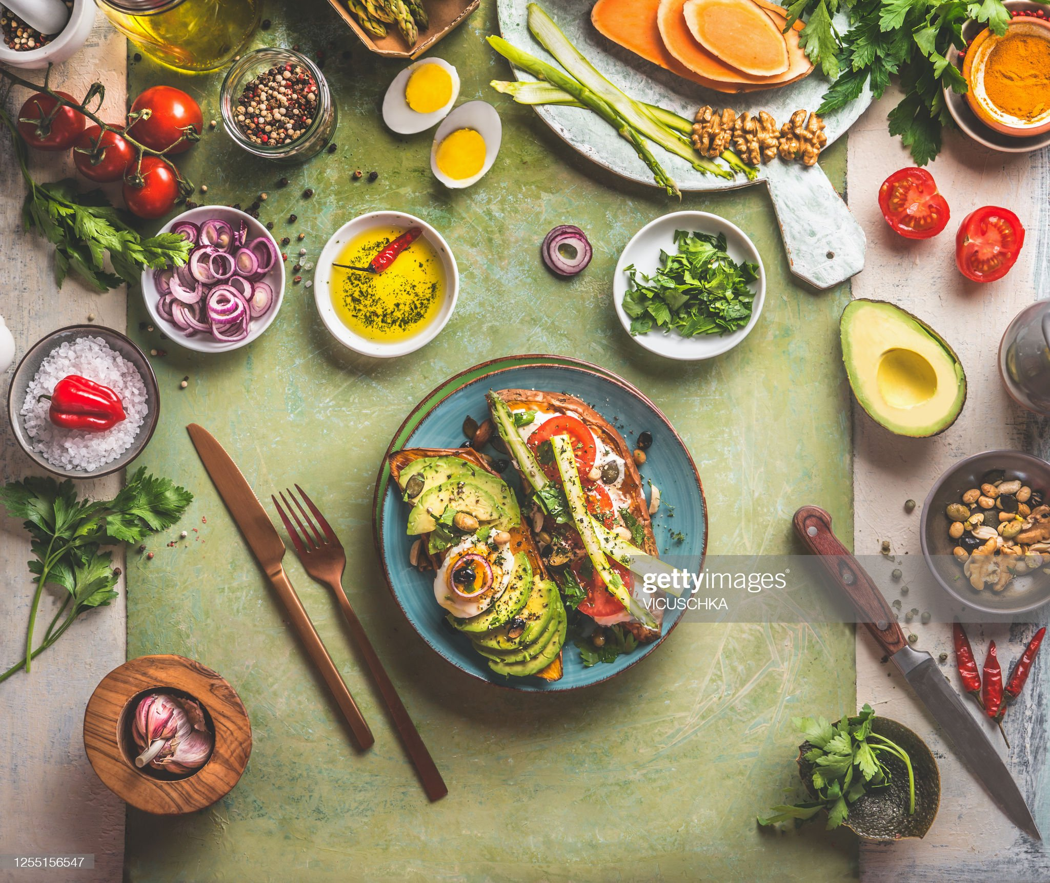 Sweet potatoes sandwich avocado, egg, tomatoes and asparagus served on green kitchen table with ingredients: fresh vegetables, seasonings, olives oil and cutlery. : Stock Photo