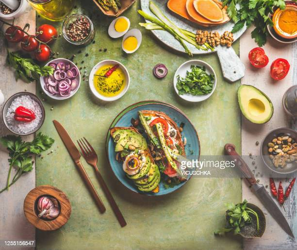 sweet potatoes sandwich avocado, egg, tomatoes and asparagus served on green kitchen table with ingredients: fresh vegetables, seasonings, olives oil and cutlery. - körperbewusstsein stock-fotos und bilder