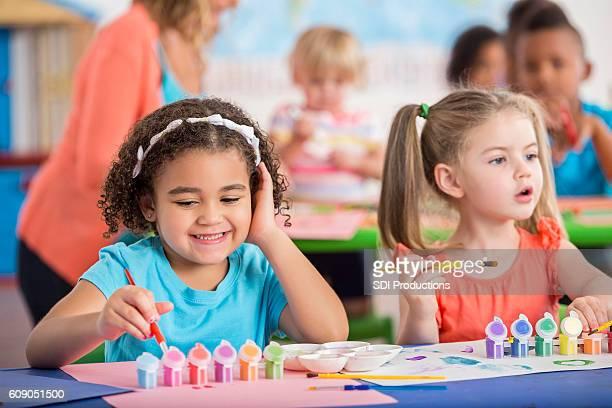 Sweet preschool friends have fun painting