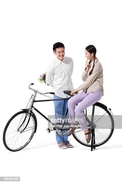 Sweet retro couple with flowers and old-fashioned bicycle