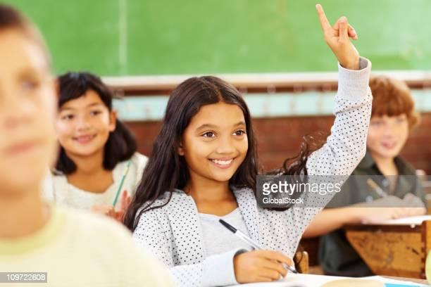 Sweet school girl raising her hand and smiling