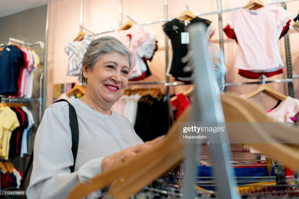 Dulce Mujer Senior Mirando Ropa En Una Tienda Sonriente Foto De Stock Getty Images