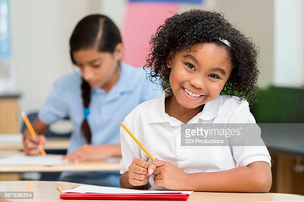Sweet smiling African American student working on homework