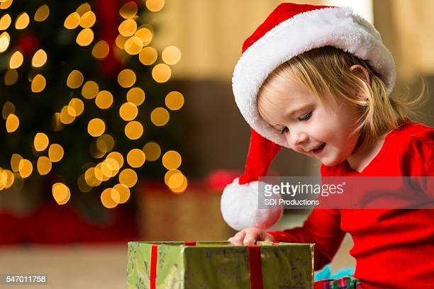 Sweet toddler girl looking into christmas box