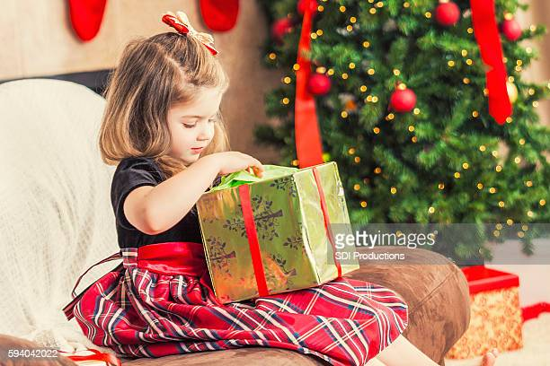 Sweet toddler girl opening gifts on Christmas morning