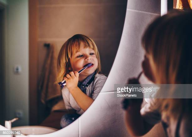 sweet young boy is brushing teeth