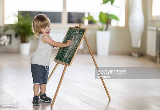 sweet young boy is having fun to write on blackboard